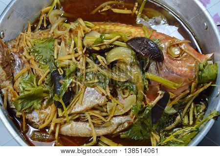 steamed fish with soy sauce topping slice ginger and mushroom in pot