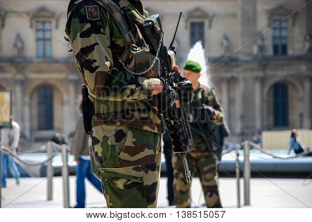 French army soldier patrolling on streets with assault rifles near Louvre in Paris, France.
