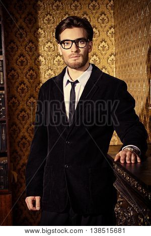 Handsome young man standing by a fireplace in a room with classic interior. Luxury. Men's beauty, fashion.