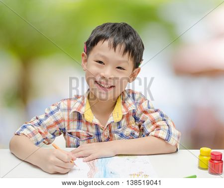 Portrait of Asian boy looking happy after finishing his artwork