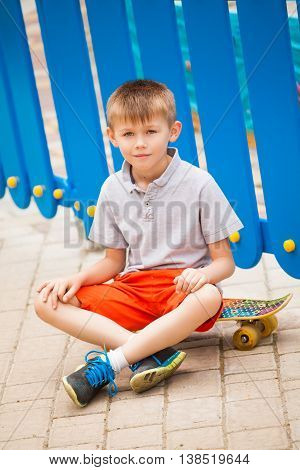 Boy sitting on a skateboard on the background of blue fence