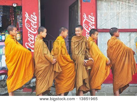 KATHMANDU, NEPAL - APRIL 12: Unidentified young monks stay in line to collect alms and offerings on April 12, 2010 in Kathmandu, Nepal. This procession is held every day.