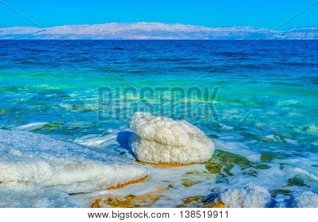 The thick layer of salt covers the stones instantly drying in the sun on the Dead Sea shore Ein Gedi Israel.