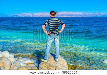 The young man on the coast of the Dead Sea watch the seascape and Jordanian mountains Ein Gedi Israel.