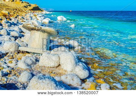 The Dead Sea's salt covers the stones and other objects lying on the shore Ein Gedi Israel.