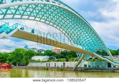 TBILISI GEORGIA - MAY 28 2016: The modern Peace Bridge looks very unusual in heart of the old town on May 28 in Tbilisi.