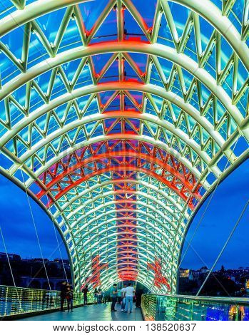 TBILISI GEORGIA - MAY 28 2016: The glass tent of the Peace Bridge illuminated in colors of National Flag of Georgia on May 28 in Tbilisi.