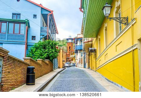 The street with the colorful cottages in Abanotubani district ends with the brick minaret of Jumah Mosque Tbilisi Georgia.