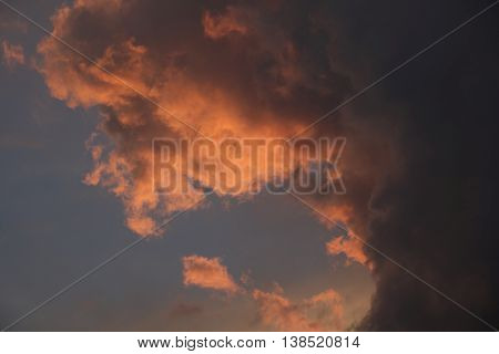 Dark storm clouds lit by the pink orange light of sunset