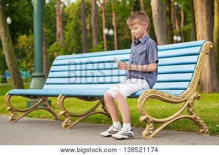 Boy listening music in headphones sitting on the bench and stares at the phone