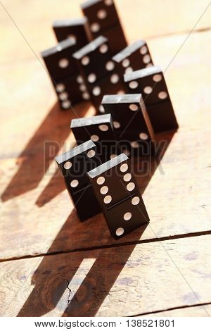 Black dominoes standing in a row on wooden background