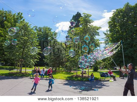 GENEVA SWITZERLAND - JUNE 17 2016: The children and with soap bubbles attraction at park in the old town of Geneva Switzerland on 28 July 2010. It is the second most populous city in Switzerland.