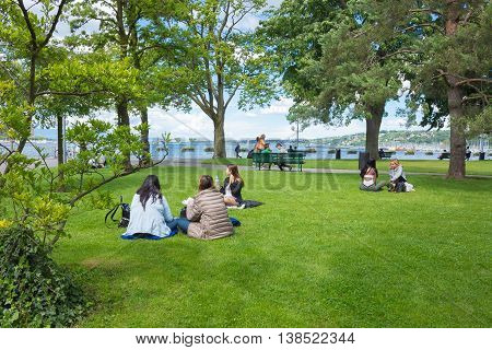 Geneva Switzerland - June 17 2016: The people sitting on the grass in a park on the waterfront of lake in the old town of Geneva Switzerland on 28 July 2010. It is the second most populous city in Switzerland.