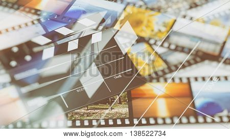 Clapperboard on filmstrips with pictures abstract background