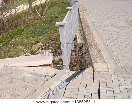 The Destruction Of The Pedestrian Walkway Of Stone Tiles, And The Brittle Behavior Of The Fence