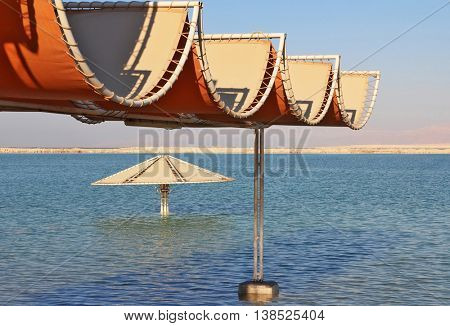 Sunny beach on the Dead Sea. A wonderful warm day in December. The beach pavilion is half flooded with seawater risen