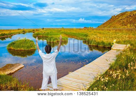 Lovely pond with thermal water. On small islands grows tall grass. Across the pond crossed by wooden walkways. Woman in white performs yoga