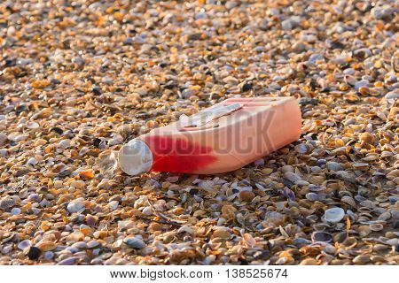 Plastic Bottles Of Engine Oil On The Beach Is Strewn With Small Colorful Sea Shells