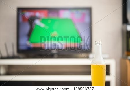 home interior with a bottle of beer in front and a TV broadcasting a snooker match at backgroud