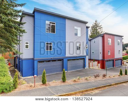 Very Modernized Apartment With Red And Blue Colors, Along With Garage And Driveway.