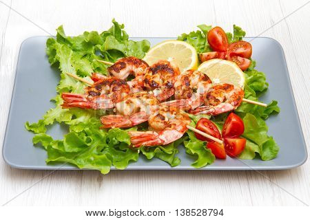 plate of grilled prawns with salad and cherry tomatoes