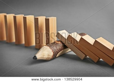 Wooden pencil blocked row of falling dominoes on grey background