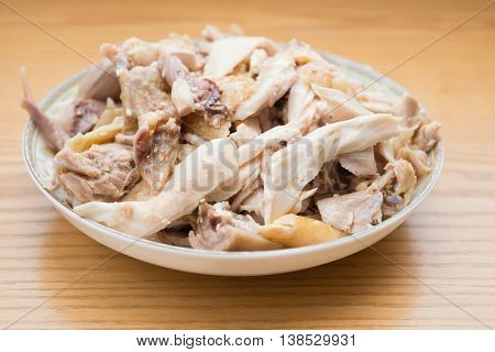 dish of shredded boiled chicken on wood table