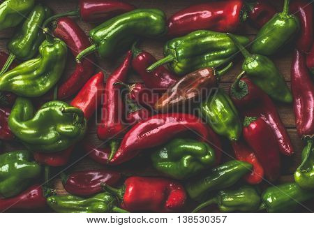 Background of colorful red and green bell peppers over wooden backdrop, top view