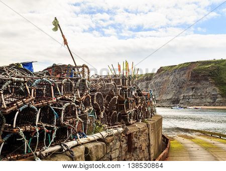 STAITHES ENGLAND - JULY 12: Lobster fishing pots stacked up on the quayside. In Staithes North Yorkshire England. On 12th July 2016.