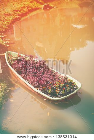 Boat With Foliage Plant And  Flowerer On Lake. Warm Tone And Vintage Picture Style.