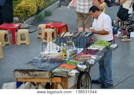 ISTANBUL - AUGUST 7: Unknown man trades food in a street near harbor, August 7, 2013 in Istanbul, Turkey. Istanbul is the world's fifth-most-popular tourist destination.