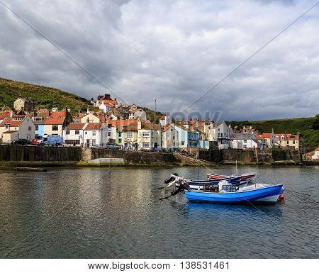 STAITHES ENGLAND - JULY 12: Fishing boat in the harbour the seafront behind. In Staithes North Yorkshire England. On 12th July 2016.