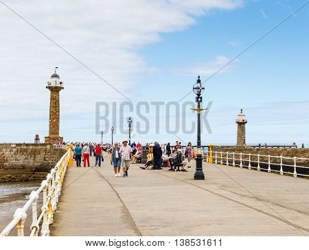 WHITBY ENGLAND - JULY 12: Lots of tourists on the West Pier. In Whitby North Yorkshire England. On 12th July 2016. In Whitby North Yorkshire England.