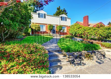 Beautiful Curb Appeal Of Two Level House With Nice Front Garden And Concrete Walkway. .