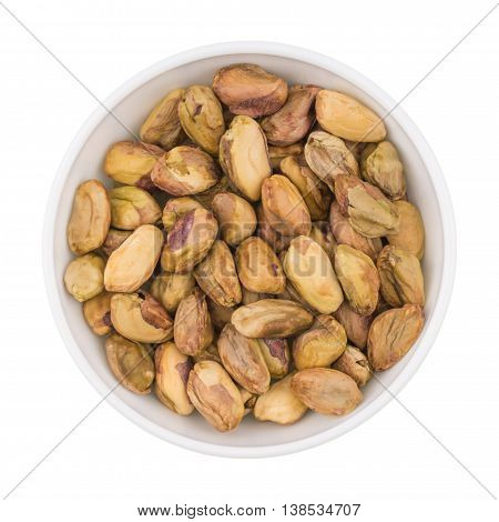 At the center of the frame white bowl with raw pistachio kernels on a white background. Raw pistachio kernels. Close. Horizontal shot. Top view.
