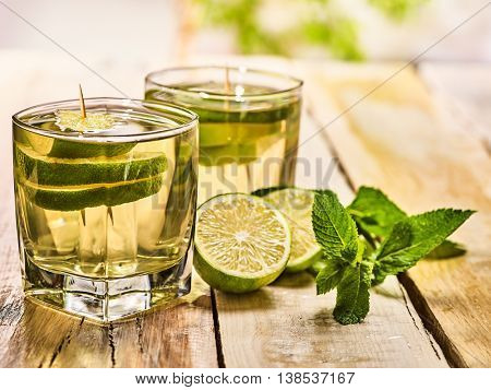 Alcohol drink. On wooden boards two glasses with alcohol green transparent drink. A drink number hundred sixty five mojito cocktail with half lime and mint . Country life style. Light background.