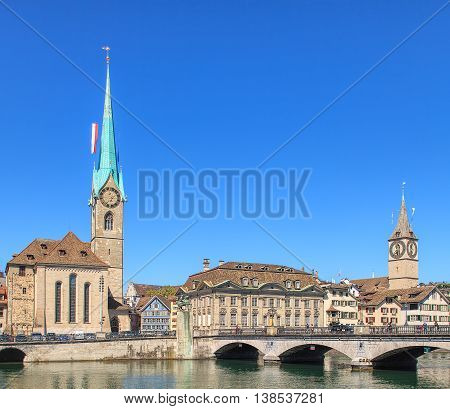 Towers of the Fraumunster Cathedral ans St. Peter Church decorated with flags and the Muensterbruecke bridge over the Limmat river in the city of Zurich, Switzerland.