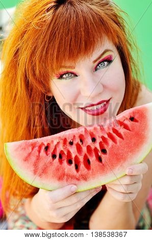 redhead bright girl with slice of fresh sweet watermelon