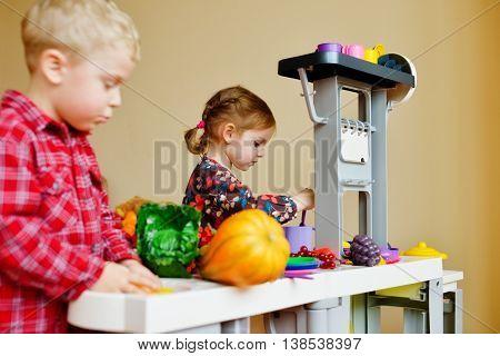 children playing toy kitchen in the kindergarten