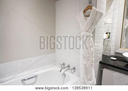 Inside the bathroom with bathtab and bathrobe