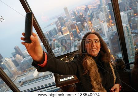 CHICAGO, IL - CIRCA MARCH, 2016: woman taking selfie at John Hancock Center's observatory. The John Hancock Center is a supertall skyscraper at 875 North Michigan Avenue, Chicago.