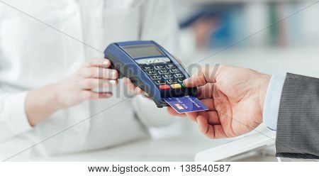 Man making purchases at the drugstore he is paying with a credit card and using a terminal