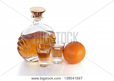Bottle with glasses of tequila and orange on white background