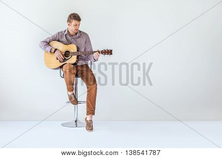 Handsome Smiling Guitarist Play Music Siting On Chair