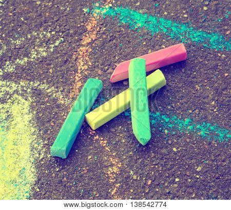 Colored chalk for drawing. Colored chalk on the playground with drawings on the street retro style