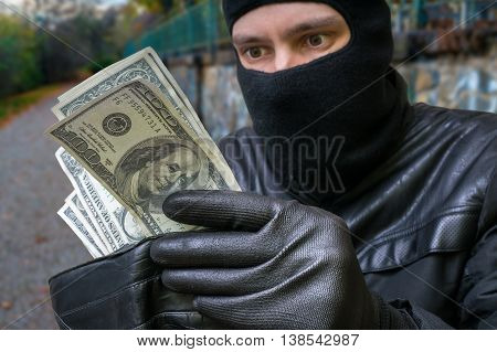 Stealing Concept. Masked Thief Is Counting Money In Stolen Walle