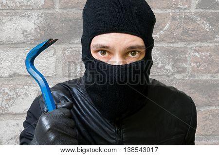 Masked burglar or thief with balaclava and crowbar.