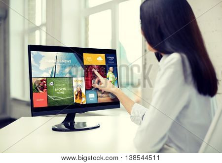 business, people, technology and mass media concept - close up of woman pointing finger to news application on computer monitor in office
