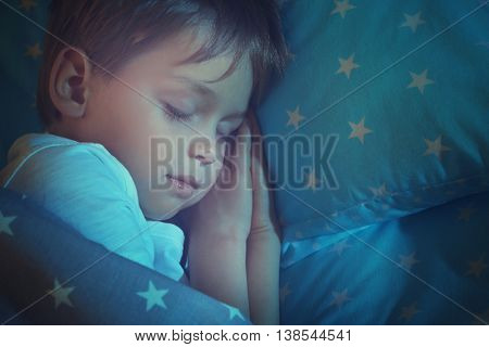 Adorable little boy sleeping in bed, close up