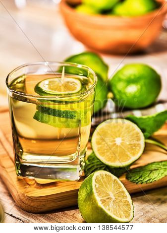 Country drink. On wooden boards is glass with green transparent drink and lime glue bowl. A drink number hundred sixty six mojito with mint leaf on sunlight . Country life. Vertical still life.